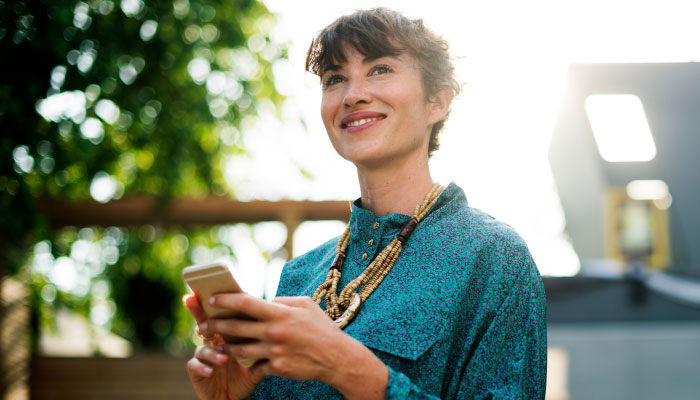 woman smiling and holding a cellphone